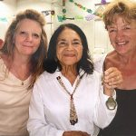 Three women lean in for a photo together at a celebration