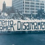 """Archival photo of Loretto members in a march. The banner they carry reads """"Loretto Women for Disarmament"""""""