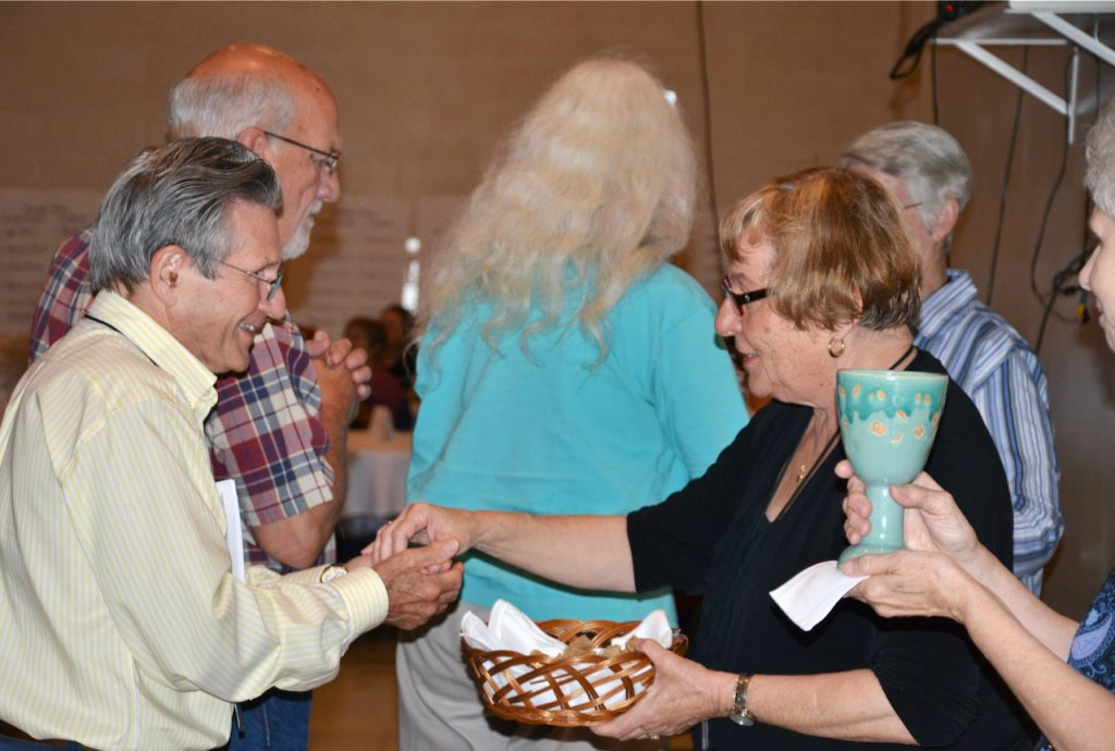 A man joyfully receives communion from a woman