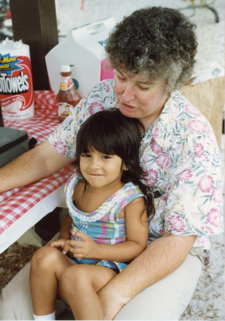 A woman sits with a small girl on her lap at a picnic table