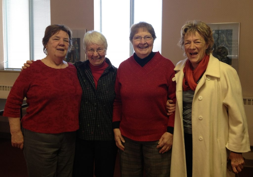 Four women stand arm and arm, smiling and laughing for the camera