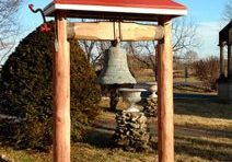 A large bell hangs outside on a wooden beam held up by two wooden posts. A cross sits atop the beam.