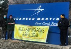 "Five people in winter clothing and face masks stand next to the Lockheed Martin sign holding a banner with the text ""Nuclear Weapons are Illegal"""