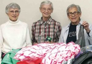 Three women stand behind boxes of donated clothing.