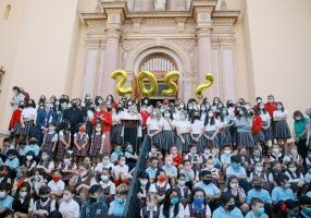 A crowd of students in school uniforms stand on the steps with balloons reading 2022