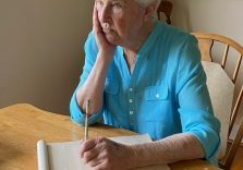 A woman sits at a table with pen and paper, contemplating what to write.