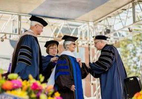 Regis University President the Rev. John P. Fitzgibbons, at right, assists Lydia Peña SL with her doctoral academic dress at the May 2019 commencement service. Regis University Board of Trustees Chairman Robert Engel is at far left. (Photo by Regis photographer Brett Stakelin)