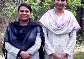 Two women in traditional Pakistani attire stand shoulder to shoulder.