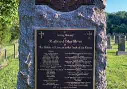 """A stone memorial with bronze plaque that reads """"In Loving Memory of Oblates and Other Slaves of The Sisters of Loretto at the Foot of the Cross"""""""