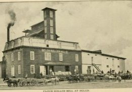 Belen, NM Flour mill in 1904. Horses, carts and workers in front of the mill.