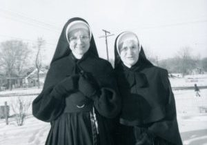 Photo of two sisters standing out in the snow in winter habits